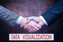 Hand writing sign Data Visualization. Business showcase representation of information in the form of a chart Two Professional Well-Dressed Corporate Businessmen Handshake Indoors