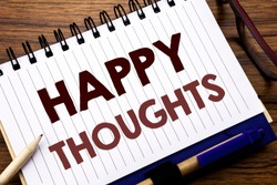Hand writing text caption inspiration showing Happy Thoughts. Business concept for Happiness Thinking Good Written on notebook paper, wooden background with glasses pen and marker.