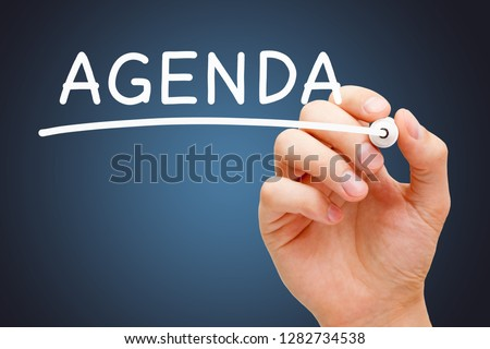 Hand writing the word Agenda with white marker on transparent wipe board over dark blue background.