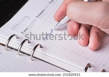 hand writing with silver pen on open business agenda