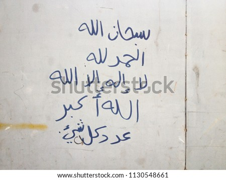 "Hand writings on dirty steel wall, by Arabic language, its mean """"God is perfect"", ""thank God"", ""There is no god but Allah"" and ""Allah is Great""."