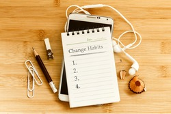 Hand written  Change habits message notepad with  pencil  on wooden table for change habits  list for good life concept , overhead shot or Top view