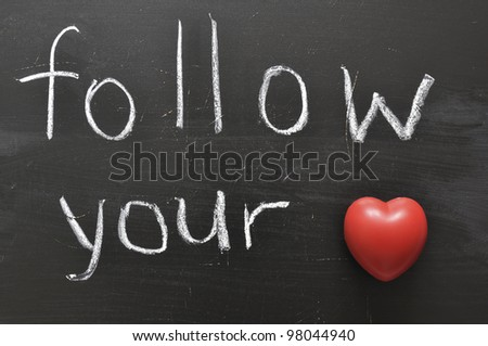 hand written follow your with red heart symbol on black chalkboard