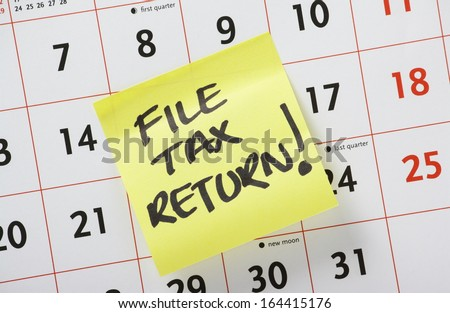 Hand written reminder to File Tax Return on a yellow post it note stuck to a calendar background