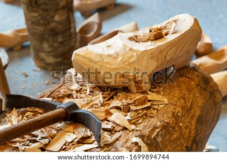 Handamade rustic wooden clog, usually with small studs on the sole and finished with a pointed upturned toe.
