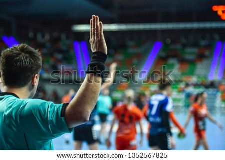 Handball referee gives signal playing for time during handball match. #1352567825
