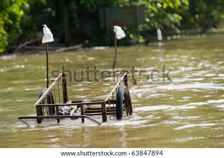 Handcart left at a flooded road in rural Thailand during the monsoon season.