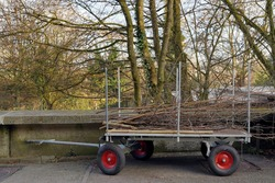 Handcart of wheelbarrow loaded with tree branches and twigs removed from the  trees in garden work in the spring. The plant waste is neatly arranged on the cart with rubber wheels.