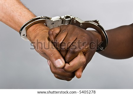Handcuffed hands, revolution comrades or hostage situations  concept, African American, Hispanic race.