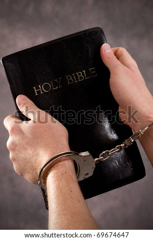 Handcuffed male hands hold a black Holy Bible.