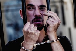 Handcuffed man smoking a cigarette imprisoned for crime, punished for serious villainy. Arrest, gangster, pain concept.