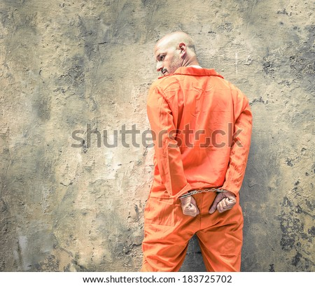 Handcuffed Prisoner in Jail waiting for Death Penalty - Guantanamo orange clothes - Grunge dramatic wall background