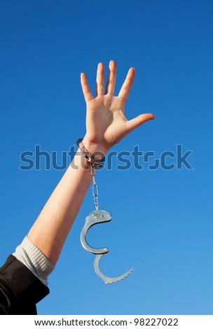 Handcuffed woman's hand against blue sky