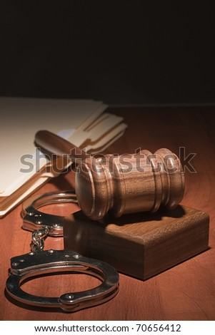 Handcuffs and a wooden gavel in front of manila folders.