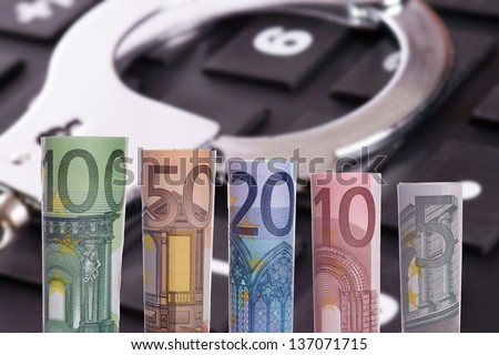 Handcuffs and Calculator with Euro bank notes / economic fraud