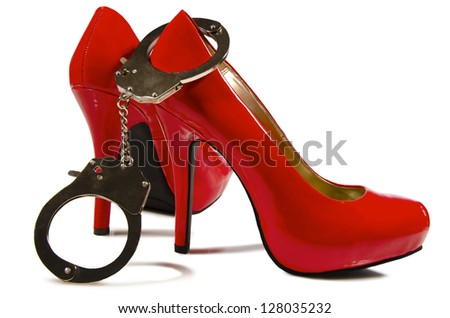Handcuffs and high heels close up, on white background.