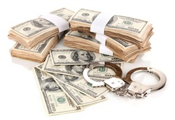 Handcuffs and packs of dollars isolated on white