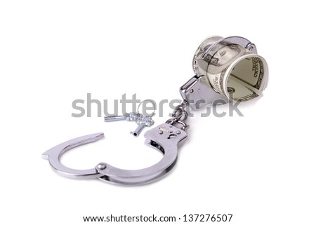 handcuffs around a roll of 100 dollar bills, concept of money tied up in something