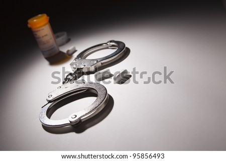 Handcuffs, Medicine Bottle and Pills Under Spot Light Abstract.