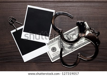 handcuffs money and old photos on wooden table detective concept