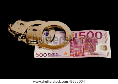 handcuffs on 500 euro banknote isolated on black