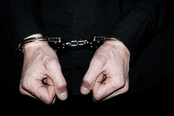 Handcuffs on hands of a arrested handcuffed criminal man in black shirt.