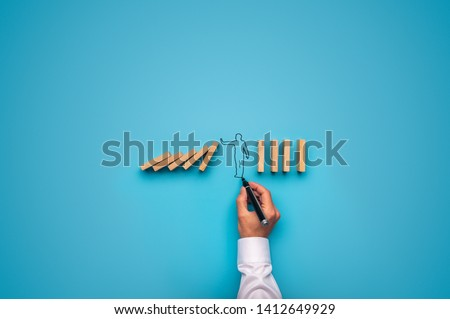 Handdrawn shape of a businessman stopping falling dominos. Over blue background.