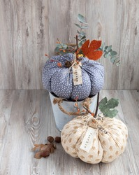 Handemade cozy  fabric pumpkins for autumn decoration. White knitted or wood background
