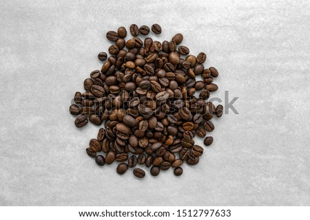 Handful of coffee beans on a gray background