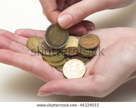 handful of euro coins in woman's hands