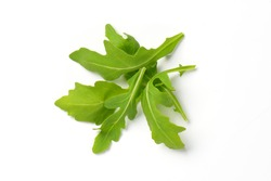 handful of fresh arugula leaves on white background