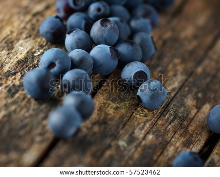 Handful of fresh blueberries on wooden surface, closeup