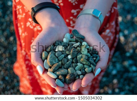 Handful of green pebbles in hands. Perfect clean pebble beaches on the coast of Liguria