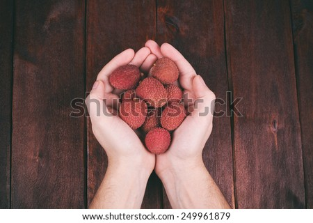 Handful of lychee, Chinese plum. Men\'s palm with lychee. Exotic fruit. Diet food. Toned image. Kitchen table and hands.