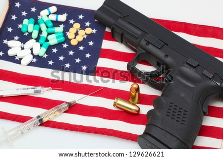 Handgun atop US flag with pharmaceuticals & two loose cartridges arrayed