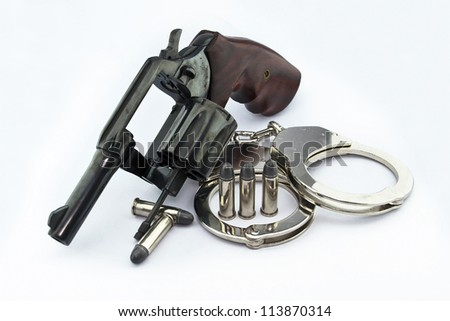 handgun revolver and police handcuff with bullets on white background