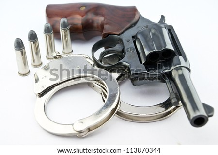 handgun revolver and police handcuff with bullets on white background - stock photo