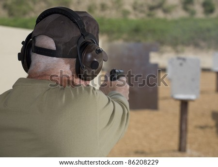 Handgun shooter readying to shoot at steel targets