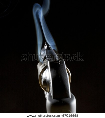 handgun that has an o ring of blue smoke near the barrel #67016665