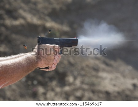 Handgun with empty brass in the air and the bullets vapor trail visible