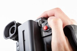 Handheld camcorder, old retro video camera object held in hand, closeup, white background, cut out. Finger on the red rec record button. Filmmaking, movie making abstract concept, first person pov