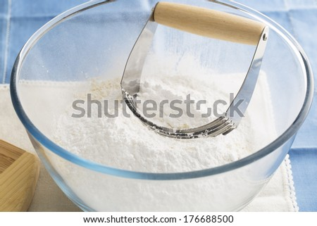 Handheld pastry blender in bowl with flour.