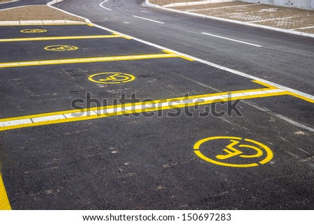 Handicap parking space just painted. Universal wheelchair symbols painted on the asphalt. Focus is on the at the first sign of wheelchair symbols.