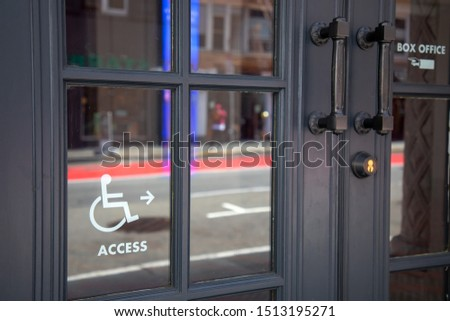 Handicapped access entrance sign on door glass at the entrance of the shop or restaurant.