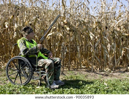 handicapped hunter in a wheelchair wearing a safety vest with a corn field in the background