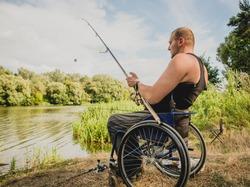 Handicapped man fishing at a lake. Wheelchair. Camping. Summertime