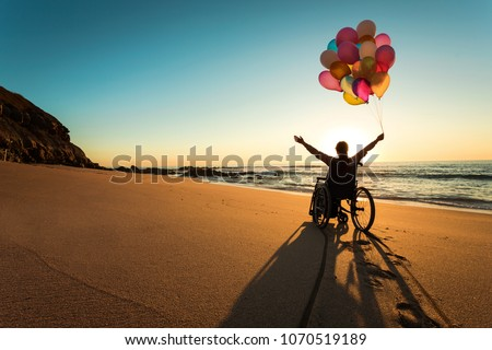 Handicapped man on a wheelchair with colored balloons at the beach