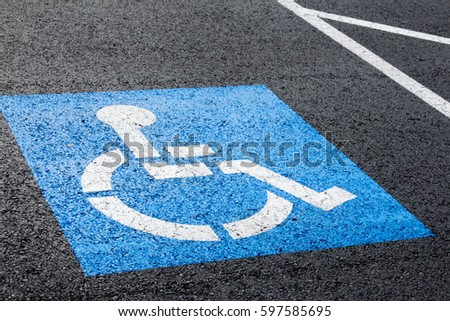 Handicapped parking spot, blue square on black asphalt