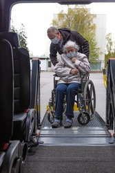 Handicapped person loading in a wheelchair into a minibus for transportation. Male driver and elderly woman in medical masks.