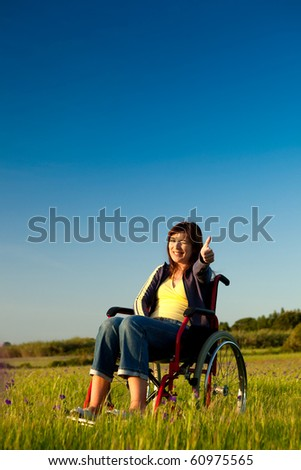 Handicapped woman on a wheelchair over a green meadow looking away